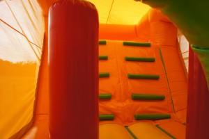 Binnenkant van een springkasteel met een klimobstakel