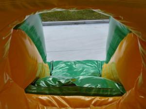 Binnenkant van een springkasteel in groene en oranje kleuren met glijbaan