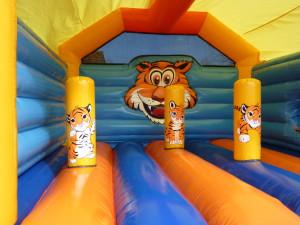 Springkasteel met oranje, gele en blauwe kleuren en tijgerfiguren
